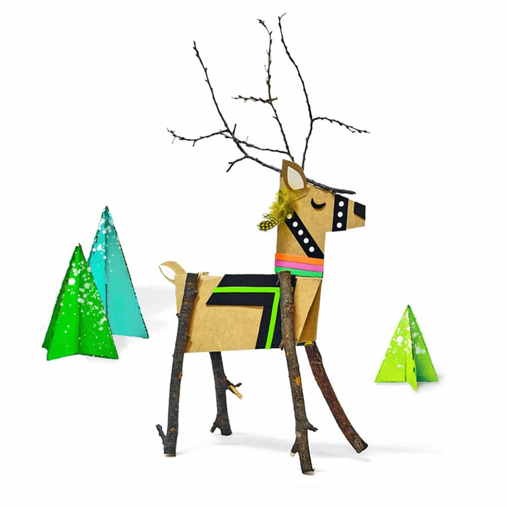 Our DIY cereal box reindeer standing among a set of mini cardboard trees.