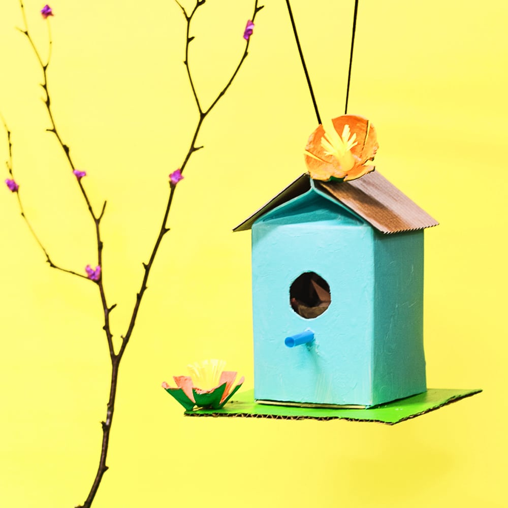 Our recycled juice carton birdhouse decorated with egg carton flowers hanging from a small branch.